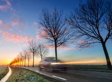 Eenzame auto op de baan bij zonsondergang