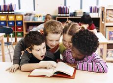 4 kindjes lezen samen een boek in het basisonderwijs