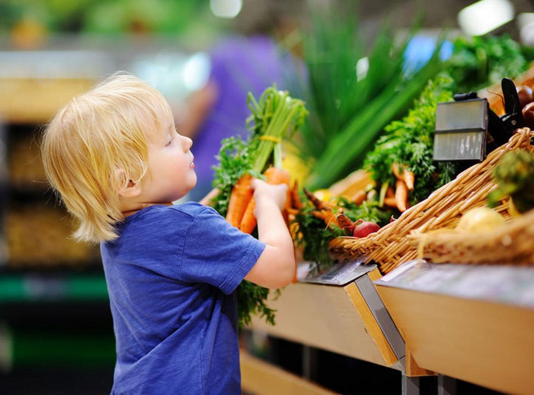 Kindje in winkel neemt groenten